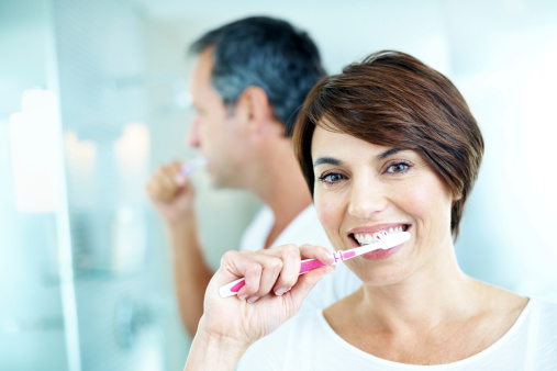 a dental implant patient from Lehigh Oral and Maxillofacial Surgery brushing her teeth